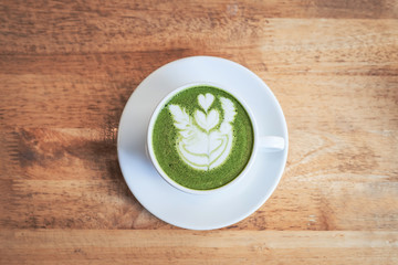 Green tea matcha latte in a cup on wooden background