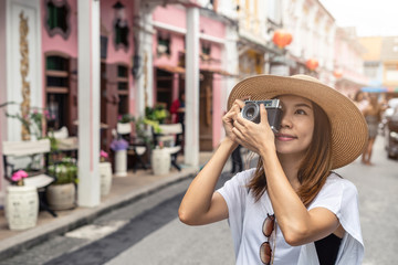 Young woman traveler walking and taking a photo at Phuket old town in Thailand