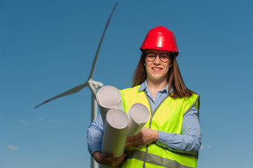 Portrait of a positive cute young female engineer in a green waistcoat and red hard hat with geodesic plans in hand against the backdrop of a windmill and blue sky.