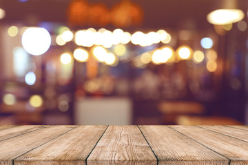 Empty wood table top with blurred light bokeh in night cafe restaurant background