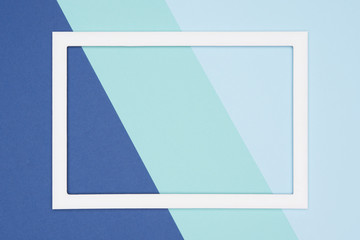 Abstract geometrical flat lay pastel blue and turquoise colored paper background. Minimalism template with empty picture frame mock up.