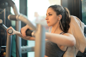 Beautiful girl listening music while training in the gym