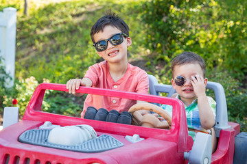 Young Mixed Race Chinese and Caucasian Brothers Wearing Sunglasses Playing In Toy Car