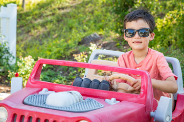 Young Mixed Race Chinese and Caucasian Boy Wearing Sunglasses Playing In Toy Car