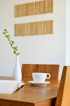white cup, book and vase on natural oak table
