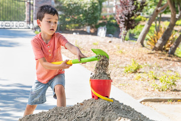 Young Caucasian and Chinese Boy Playing with Shovel and Bucket