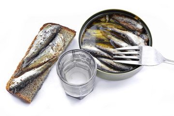 Full open round tin jar of canned golden smoked Baltic sprats in oil, sandwich with it, fork and shot of strong vodka. Top view. White background. Isolated