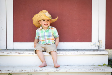 Young Mixed Race Chinese and Caucasian Boy Wearing Cowboy Hat Relaxing On The Steps