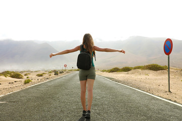 Freedom flying woman in free happiness bliss in empty asphalt desert road. Happy female traveler backpacker enjoying silence in desert road during travel holidays vacations in Lanzarote. Low angle.
