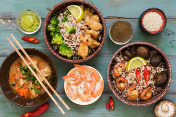 Rice with prawns, chicken, mushrooms, broccoli on a naked rustic background. Asian dishes. Concept of Asian food. Flat lay.