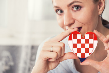 Young woman with gingerbread heart cookies with flag of Croatia