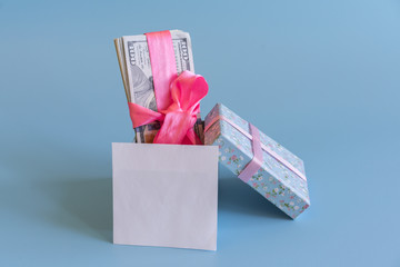 U.S. dollars banknotes laying in bow decorated gift box. Opened gift and dollars. Gift box with banknote of dollar. White sheet for your lettering