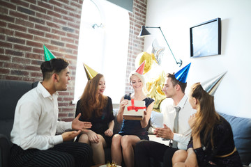 Several young people in birthday caps looking at present in unpacked gift-box held by one of girls