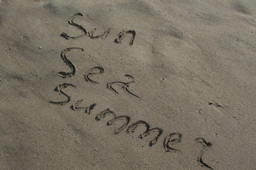 the lettering on the sand sun, sea, summer