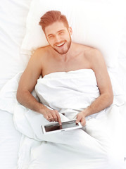 background image of man with digital tablet in the bedroom