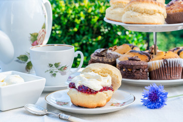Afternoon tea with cakes and traditional English scones with strawberry jam and clotted cream set up on a table in the garden. Outdoor dining.