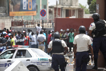 Haitian National Police guard a commercial area that was looted during protests against fuel price increases in Port-au-Prince
