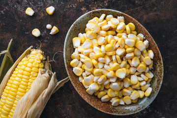 Corn kernels in a ceramic bowl next to fresh corn on the cob on dark rustic background
