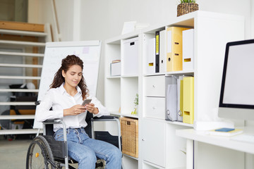Female office worker in wheelchair texting in smartphone at break in the middle of working day