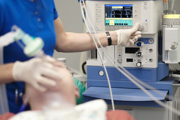 An anesthesiologist monitors the condition of a patient under general anesthesia