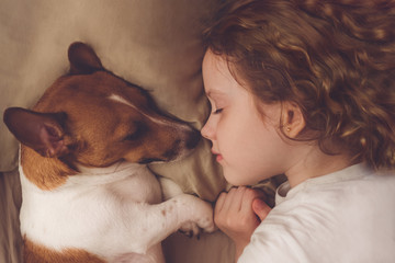 curly girl and jack russell dog is sleeping in night.