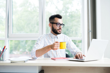 Portrait of trendy bearded businessman working at desk in office using laptop and enjoying cup of coffee, copy space