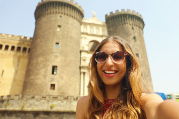 Smiling hipster woman with sunglasses taking selfie photo in Naples with Castel Nuovo castle on the background, Naples, Italy