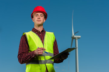 Positive young male chief engineer with a red helmet and green waistcoat signs the project agreement against a background of windmills and a blue sky