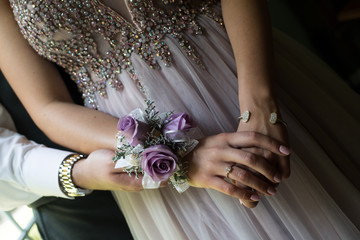 Close up of prom or weeding couple, focusing on an elegant girl's hands, with a diamond ring and crystal bracelet. Woman is wearing a purple dress with crystal beads, and a purple rose corsage.