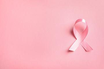 Pink ribbon on color background, top view. Cancer awareness