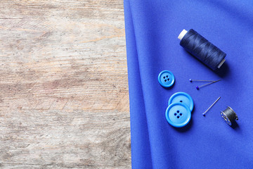 Set of tailoring accessories and fabric on wooden background