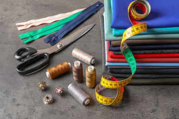 Bobbins with threads, measuring tape and stack of colorful fabrics on table. Tailoring accessories