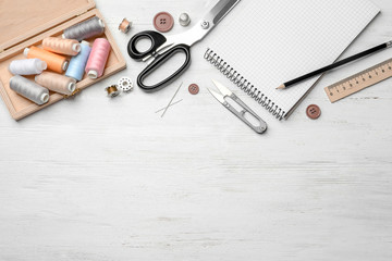 Flat lay composition with accessories for tailoring on wooden table