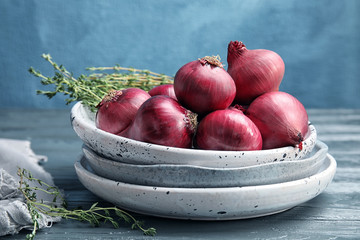 Plates with ripe red onions on wooden table