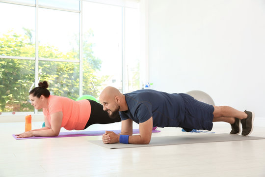 Overweight man and woman doing plank exercise on mats in gym