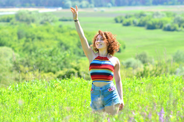 Girl waves her hand in a clearing in the open air