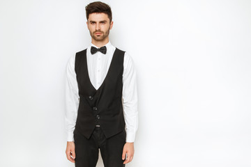 Strong commercial male model face in tuxedo on white background