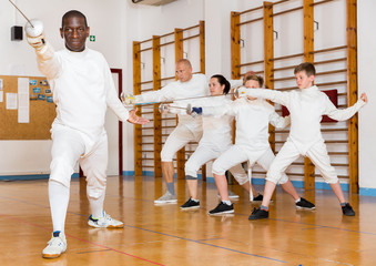 African American wearing fencing uniform practicing with foil