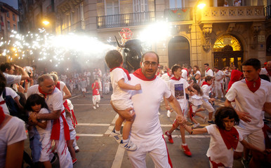 Revellers run from the Fire Bull, a man carrying a bull figure packed with fireworks, at the San Fermin festival in Pamplona