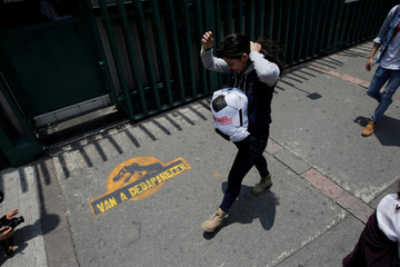 A woman walks next to a graffiti as demonstrators hold a protest outside the Institutional Revolutionary Party (PRI) headquarters in Mexico City