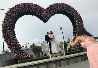 A newly-wed couple kiss as they pose for pictures in Moscow