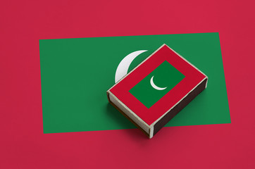 Maldives flag  is pictured on a matchbox that lies on a large flag
