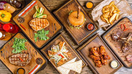 Assorted meat dishes. Burger, fried chicken breast, rib eye Steak, chicken Salad, Chicken wings, potatoes in the country and a rack of lamb on a wooden table