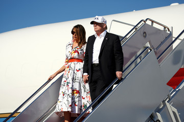U.S. President Donald Trump and U.S. first lady Melania Trump walk from Air Force One as they return from Bedminster, New Jersey, at Joint Base Andrews in Maryland