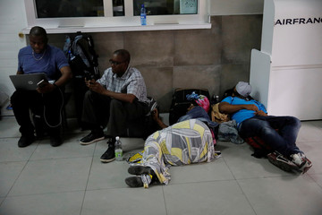 People wait for information as several flights are cancelled at Toussaint Louverture International Airport in Port-au-Prince