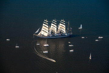 A large sailboat, bark goes into the sea surrounded by many yachts. The last windjammer bark Kruzenstern.