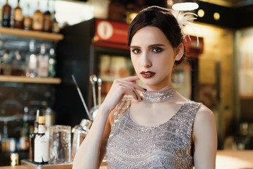 Close-up portrait of a young attractive woman in a 1920s style at the bar. Model with a beautiful make-up