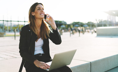 Professional journalist female talking by a mobile phone with the editor while sitting outdoors with opened laptop on her knees. Freelancer making calls by a mobile phone while spending time outdoors.