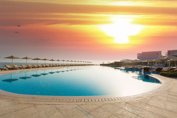 Hotel swimming pool, outdoor, with sunbeds around, sunset