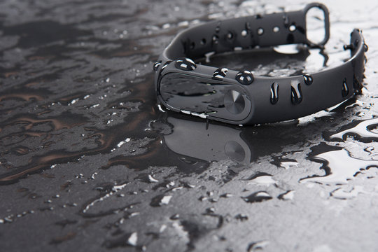Fitness bracelet on a black slate background with drops of water